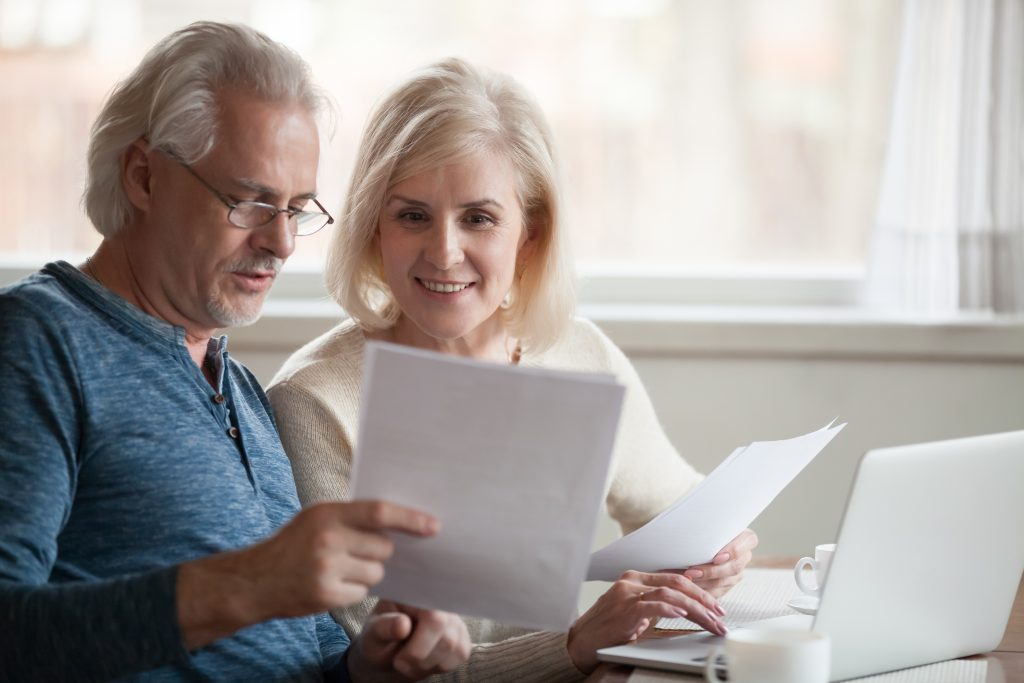 Older age couple looking at documents with open laptop